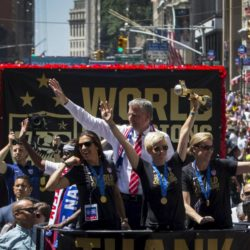 "U.S. women's soccer player Megan Rapinoe (C) holds the Wold Cup trophy as she rides a float with team mate Carli Lloyd (L) Coach Jill Ellis (R) and New York City Mayor Bill de Blasio (back C) during the ticker tape parade up Broadway in lower Manhattan to celebrate their World Cup final win over Japan in New York, July 10, 2015. Screams and a blizzard of confetti cheered the World Cup winning U.S. women's soccer players as they rolled up New York City's ""Canyon of Heroes"" on Friday in the first ticker-tape parade honoring a women's sports team. REUTERS/Mike Segar"