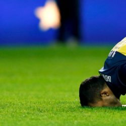 Argentine soccer striker Carlos Tevez kisses the grass of the soccer field during his presentation as a new Boca Juniors player at La Bombonera stadium in Buenos Aires July 13, 2015. Tevez was officially unveiled on Monday in a 6.5 million euros ($7.15 million) transfer from Juventus. Thousands of fans of the popular club from the port district of La Boca packed La Bombonera stadium to welcome Tevez home from a decade abroad the day after the team went top of the Argentine league championship. REUTERS/Marcos Brindicci      TPX IMAGES OF THE DAY
