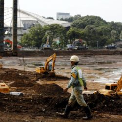 A worker walks past excavators at the construction site of Japan's new National Stadium in Tokyo July 17, 2015. Japan's new National Stadium has been ditched as the main venue for the 2019 Rugby World Cup because its proposed design will be scrapped to cut costs and it won't be ready in time, Prime Minister Shinzo Abe said on Friday. REUTERS/Thomas Peter