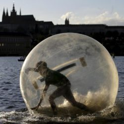 A man plays inside a giant plastic ball, called Zorb on the Vltava river as temperatures hovered over 34 degrees Celsius (93 degrees Fahrenheit) in Prague, Czech Republic, July 21, 2015. REUTERS/David W Cerny
