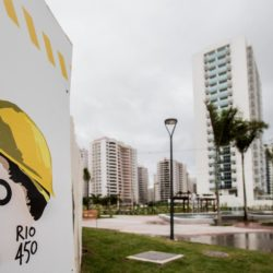 (150722) -- RIO DE JANEIRO, July 22, 2015 (Xinhua) -- The image marking the 450th Anniversary of the founding of the city of Rio de Janeiro is seen on a sign at the construction site of the Olympic and Paralympic Village in Rio de Janeiro, Brazil, July 21, 2015. The Rio 2016 Olympic and Paralympic Village situates in the Barra da Tijuca area, southwest of the city Rio de Janeiro. The village is constructed next to the Barra Olympic Park, which will be the heart of Rio 2016 Games. The construction of the 475,000 squaremeters residential complex has 31 buildings, each with 17 floors, and divided into seven condominiums. The 3,604 apartments and 10,160 bedrooms will have a total capacity of 18,000 guests.      After construction work is completed, the process of transforming the buildings into the residential complex will begin. Temporary structures will include a health centre, a cafeteria with space for 5,000 diners and a gym. By now the village is 85 percent completed, and it is scheduled to be fully operational and opened to guests from 9 o'clock of July 24, 2016.(Xinhua/Xu Zijian)(wll)