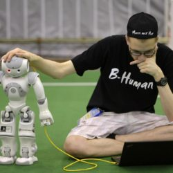 """A member from a German team adjusts a humanoid robot during the 2015 Robocup finals in Hefei, Anhui province, July 22, 2015. The Robocup, or """"Robot Soccer World Cup"""", is an annual international robotics competitions which is held between July 17 - 23 this year in China's Hefei.  REUTERS/Stringer  CHINA OUT. NO COMMERCIAL OR EDITORIAL SALES IN CHINA"""