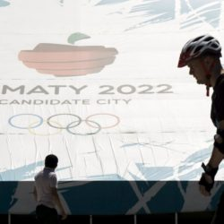 People walk past a banner promoting Almaty candidate city for 2022 Winter Olympic Games at the Medeu skating oval in Almaty, Kazakhstan, July 26, 2015. Kazakhstan is aspiring to host the 2022 Winter Olympics but many in the Central Asian nation view the bid as yet another vanity project of long-ruling President Nursultan Nazarbayev. Almaty, the financial capital, will go head-to-head with the Chinese metropolis Beijing on Friday when the International Olympic Committee elects the winner at its session in Malaysia. Picture taken July 26, 2015. REUTERS/Shamil Zhumatov