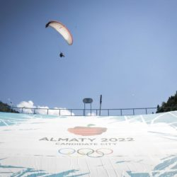 A paraglider flies over a banner promoting Almaty candidate city for 2022 Winter Olympic Games at the Medeu skating oval in Almaty, Kazakhstan, July 26, 2015. Kazakhstan is aspiring to host the 2022 Winter Olympics but many in the Central Asian nation view the bid as yet another vanity project of long-ruling President Nursultan Nazarbayev. Almaty, the financial capital, will go head-to-head with the Chinese metropolis Beijing on Friday when the International Olympic Committee elects the winner at its session in Malaysia. Picture taken July 26, 2015. REUTERS/Shamil Zhumatov